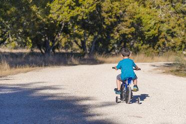 USA, Texas, Little boy riding bike with stabilisers - ABAF001195