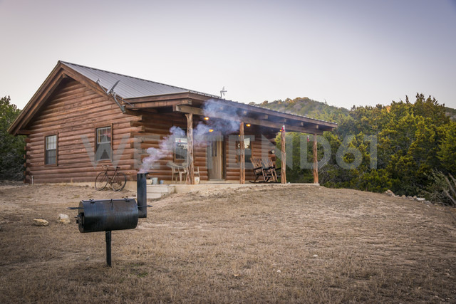 USA, Texas, Log home with barbecue smoker in front - ABAF001200 - André Babiak/Westend61