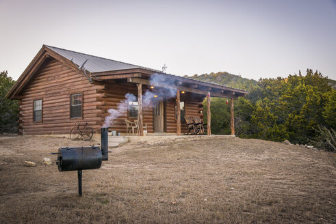 USA, Texas, Log home with barbecue smoker in front - ABAF001200
