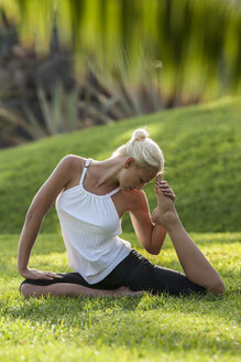 Woman practicing yoga on meadow - EGF000119