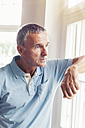Mature man leaning on window and looking outside - MFF000847
