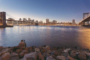USA, New York City, Man photographing Manhattan Bridge and Brooklyn Bridge - MF000868