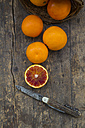 Half and whole blood oranges and pocket knife on wooden table - LVF000565