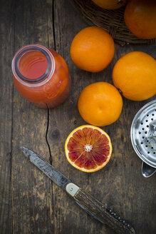 Half and whole blood oranges, bottle of blood orange juice and pocket knife on wooden table - LVF000567