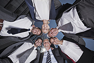 Group of smiling businesspeople in a huddle - CHAF000083
