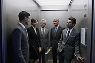 Group of businesspeople discussing in elevator - CHAF000048
