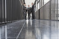 Group of businesspeople talking in hallway - CHAF000093