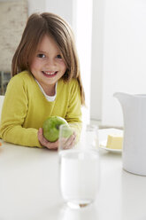 Germany, Munich, Girl sitting at table with green apple - FSF000180