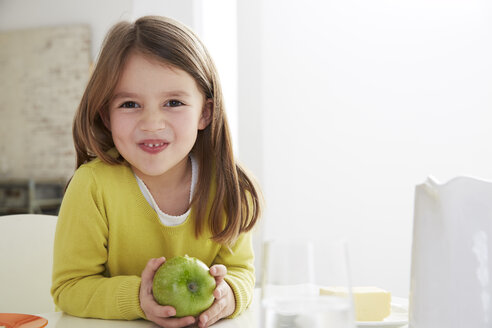 Germany, Munich, Girl sitting at table with green apple - FSF000177