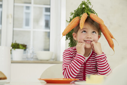 Germany, Munich, Girl sitting at table with bunch of carrots on head - FSF000174