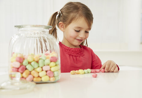 Germany, Munich, Girl with candy jar, counting candies - FSF000162