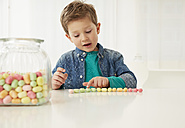 Germany, Munich, Boy with candy jar, counting candies - FSF000153