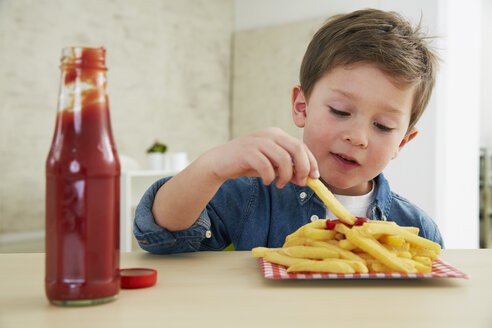 Germany, Munich, Boy eating French fries with ketchup - FSF000193