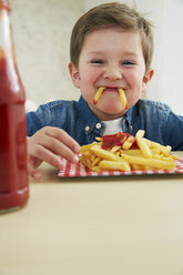 Germany, Munich, Boy eating French fries with ketchup - FSF000195