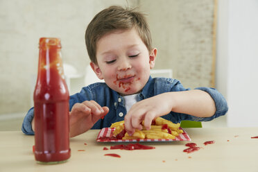 Germany, Munich, Boy eating French fries with ketchup - FSF000199