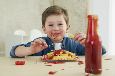 Germany, Munich, Boy eating French fries with ketchup - FSF000192