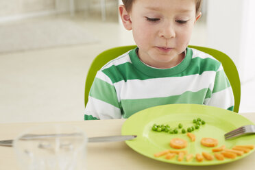 Germany, Munich , Boy eating peas and carrots showing anthropomorphic face - FSF000147