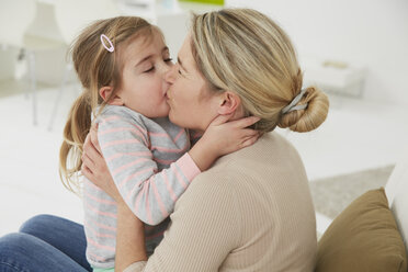 Germany, Munich, Mother and daughter sitting on sofa, cuddling - FSF000124