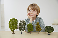Germany, Boy sitting at table with tree models, environmental conservation - FSF000108