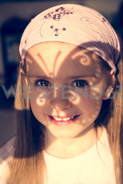 Portrait of smiling little girl with butterfly shaped shadow on her face - SARF000251 - Sandra Rösch/Westend61