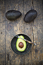 Two whole and a half avocado (Persea Americana) on wooden table - LVF000592