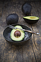 Sliced and whole avocados (Persea Americana) on wooden table - LVF000593