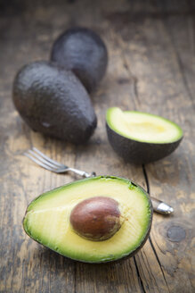 Sliced and whole avocados (Persea Americana) on wooden table - LVF000594