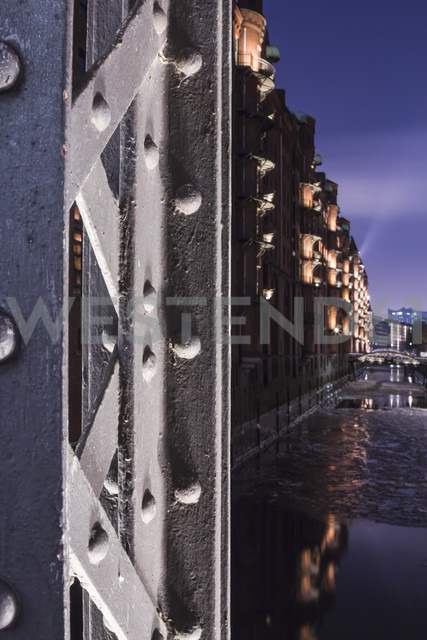 Germany, Hamburg, Illuminated Pillar of a girder bridge in the historic warehouse district - NKF000053