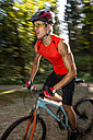 Germany, Mountainbiker in forest - EGF000092