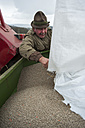 Germany, Rhineland-Palatinate, Neuwied, farmer filling artificial fertilizer into tractor - PA000364