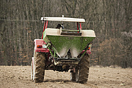 Germany, Rhineland-Palatinate, Neuwied, farmer sowing artificial fertilizer with tractor - PA000379
