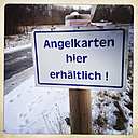 Sign for fishing cards at snowy road, Brandenburg, Germany - ZMF000196