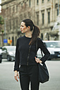 Spain, Catalunya, Barcelona, young black dressed businesswoman walking along a street - EBSF000002