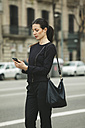 Spain, Catalunya, Barcelona, young black dressed businesswoman with smartphone in front of a street - EBSF000006