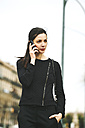 Spain, Catalunya, Barcelona, young black dressed businesswoman telephoning in front of a street - EBSF000011