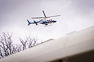 USA, Texas, Air life support helicopter approaching landing pad on top of hospital building - ABA001235