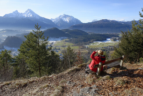 Germany, Upper Bavaria, Berchtesgaden, Maria Gern, Watzmann and Hochkalter from view point Marxen, female hiker sitting on bench - LB000538