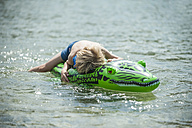 Young boy with have a rest on his swim toy - PAF000361