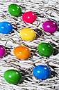 Rows of shiny coloured Easter eggs on white paper stripes - MAEF007781