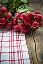 Bunches of red radishes on kitchen towel and wooden table - LVF000597
