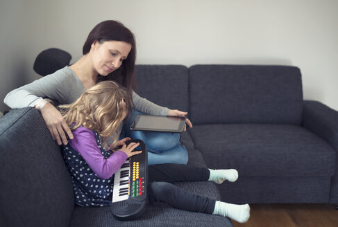 Young mother sitting with her little daughter on a couch - MW000004