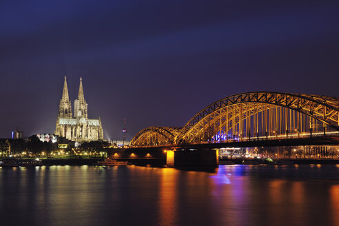 Germany, North Rhine-Westphalia, Cologne, view to lighted Hohenzollern Bridge and Cologne Cathedral by night - RUEF001219