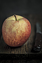 Apple with water drops and knife on chopping board - SBDF000568