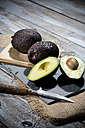 Sliced and whole avocados (Persea americana), baking paper, knife and slate on jute and wooden table - MAEF007852