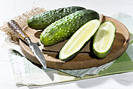 Sliced and whole cucumbers (Cucumis sativus) with knife on chopping board - MAEF007827