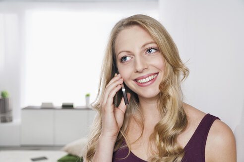 Portrait of young woman leaning against wall telephoning with smartphone - PDF000644