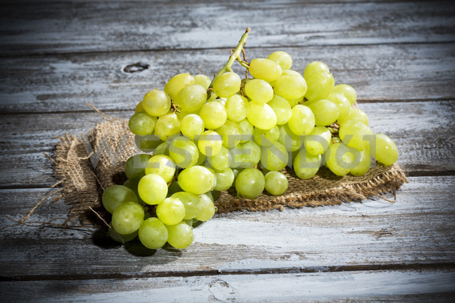 Seedless white grapes on jute and wooden table - MAEF007856