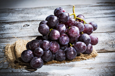 Red grapes on jute and wooden table - MAEF007858