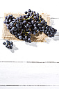 Seedless blue grapes on jute and white wooden table - MAEF007868