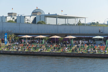 Germany, Berlin, people relaxing at riverside, Reichstag in the background - LA000563